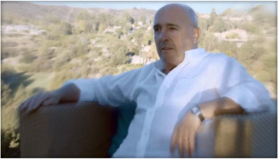 international telenovela author Enrique Torres sitting outside his home backyard, wearing a white shirt